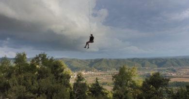 Camilla Bendazzoli che penzola con la corda dopo aver affrontato un tiro con dietro un bel paesaggio collinare
