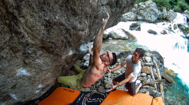 Alessandro Palma impegnato a fare Boulder vicino a un fiume